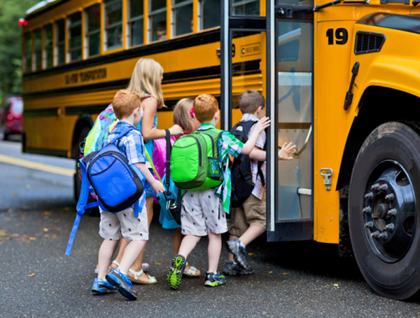 Elementary school children with backpacks getting on a school bus