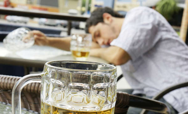 College student slumped over a table, either asleep or passed out from drinking beer