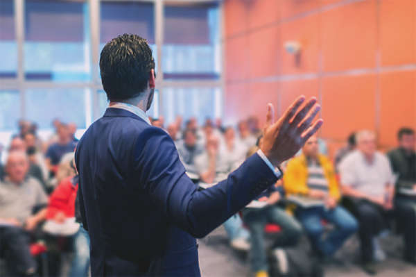 Man speaking before a group of people