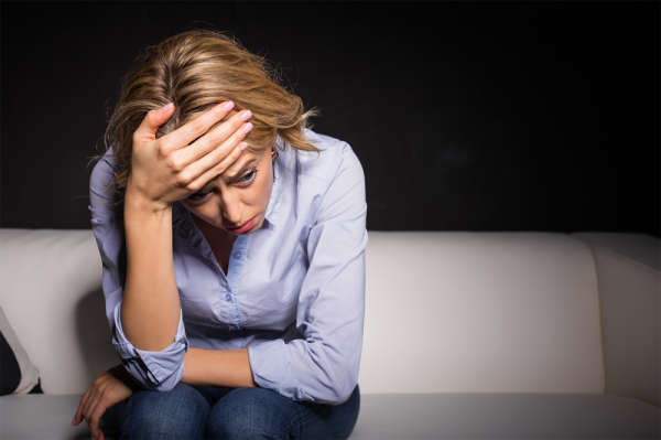 Women with anxiety and depression sitting on a sofa, with her head in her hands
