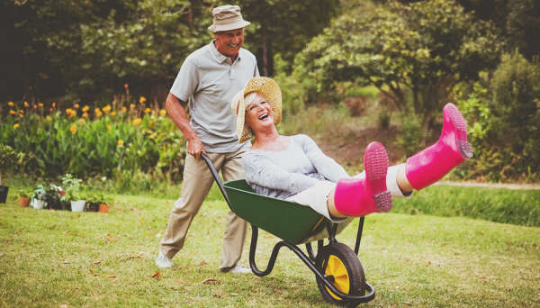 Older gentleman pushing a woman in a wheelbarrow