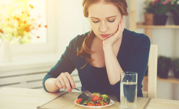 woman at dining room table eating vegetables and foods  with unsaturated fats