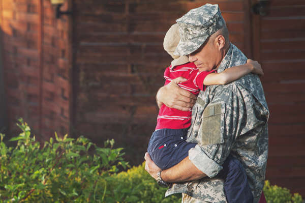 uniformed soldier holding his young son