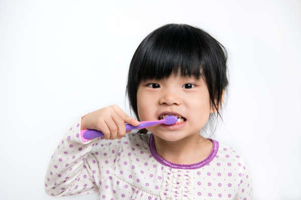 Young child, in pajamas, brushing teeth