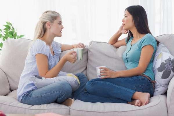 two women sitting on a sofa, drinking coffee